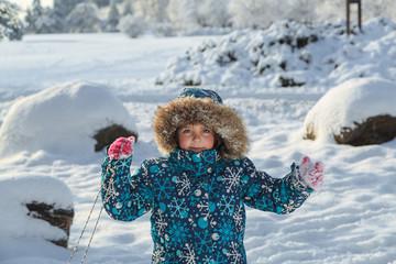 Joyfull little girl in winter park on sunny beautifull fresh day