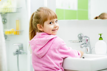 child girl washing her face and hands in bathroom