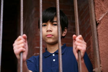 Boy standing behind bars