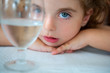 big blue eyes toddler girl looking at camera from a water cup