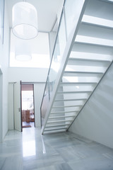 Modern white house entrance hall lobby with stairway