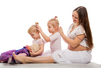 The pregnant woman and girls braid hair