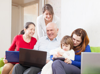 Happy multigeneration family uses few portable electronic commun