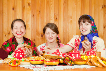 Women in traditional  clothes eating pancake