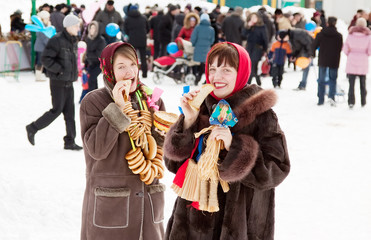 girls in russian traditional kerchief eating pancake