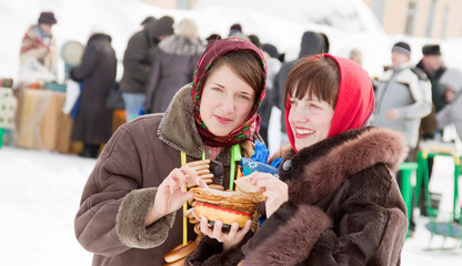 Women tasting pancake  during  Shrovetide