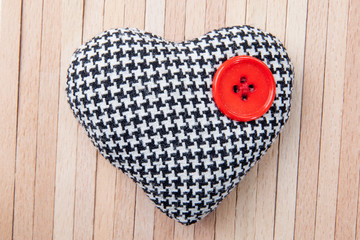 heart with red button over a wooden background