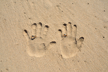 Hands print with wedding rings on sand.Wedding travel, marriage.