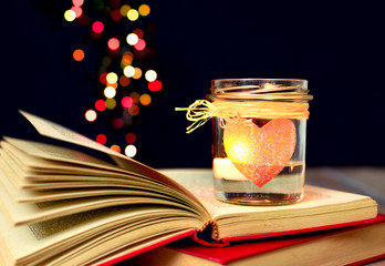 Romantic background, heart candle, open book bokeh lights.