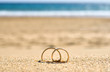 Wedding rings on sand, beach wedding travel. - 60820866