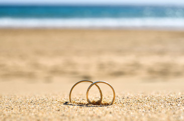Wedding rings on sand, beach wedding travel.