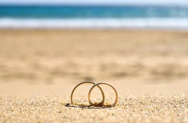 Wedding rings on sand, beach wedding travel.