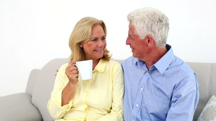 Senior couple with coffee cup sitting on sofa