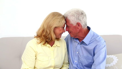 Smiling retired couple being affectionate on the couch