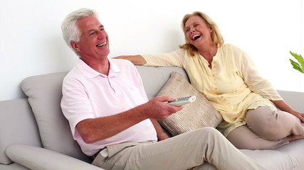 Retired smiling couple watching television on the couch