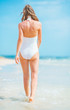 Young woman in swimsuit walking at seaside. rear view