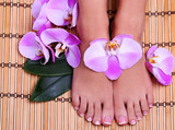Fototapety Pedicure with pink orchid flowers on bamboo mat. Beautiful