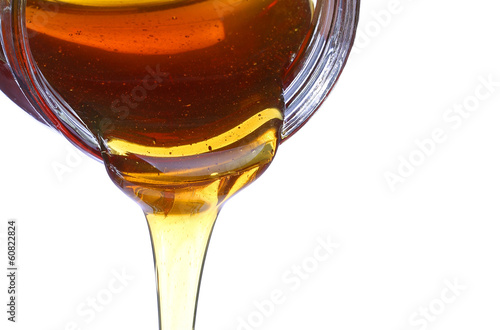 Honey spill from glass jar isolated on white