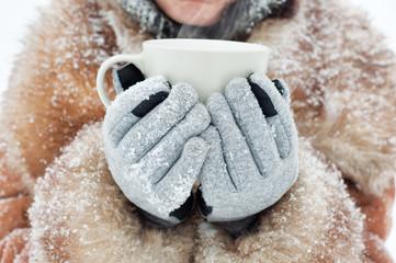Winter woman holding a mug to get warm