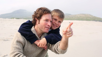 Man piggybacking his son at beach