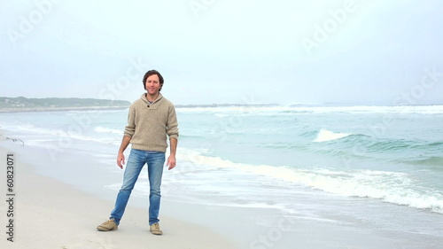 Happy man running towards camera on the beach