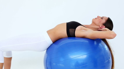 Fit model doing sit ups on exercise ball