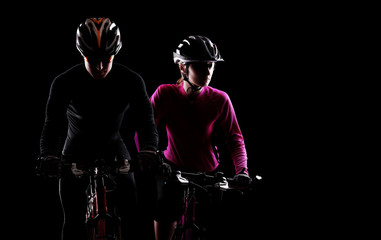 low key silhouette of a man and a girl cyclists
