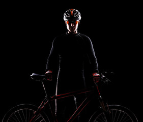 Silhouette of a cyclist holding the bicycle