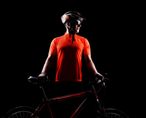 Silhouette of a cyclist looking to the copy space area