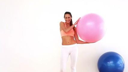 Fit model holding exercise ball and smiling at camera