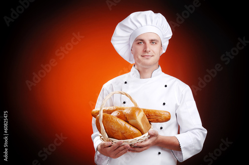 baker standing with bread in hands on dark background