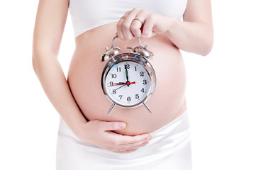 Pregnant woman belly with an alarm clock