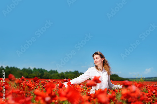 Beautiful young woman walking in a poppy field