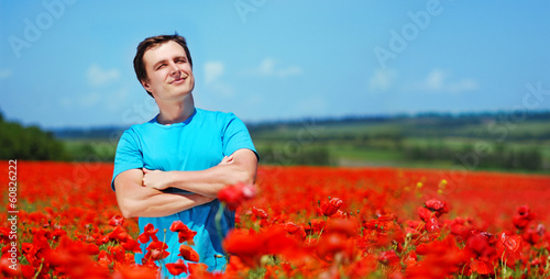 Young man standing in poppy field looking to the sky