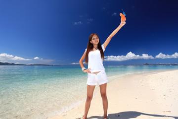 ビーチでジュースを飲む笑顔の女性