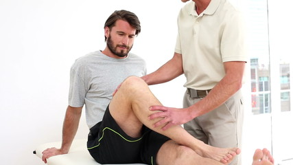 Physical therapist checking injured patients knee