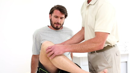 Physical therapist checking patients knee