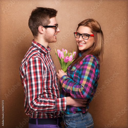 Beautiful young couple hug each other, the girl holding bouquet