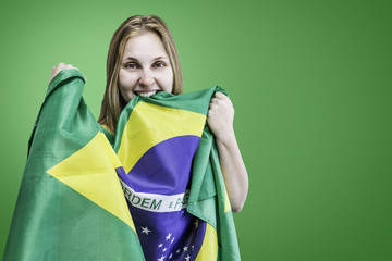 Blonde Woman holds the flag of Brazil on green background