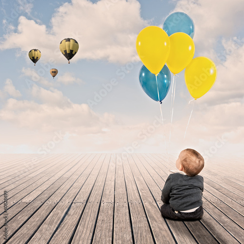 baby boy holding bunch of balloons