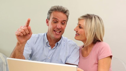 Mature couple shopping online together on the couch