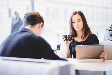 Detached couple using tablet computer in coffee shop