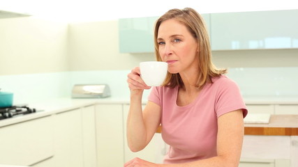 Mature woman drinking coffee and reading newspaper