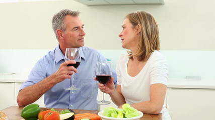 Mature couple drinking red wine together and chatting