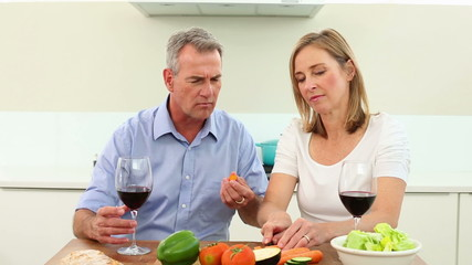 Mature couple drinking red wine together and making a salad