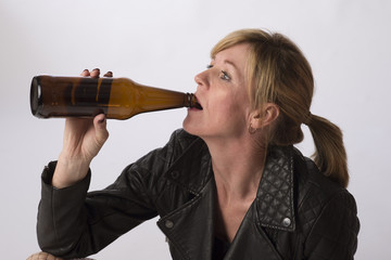 Woman drinking from a brown beer bottle