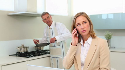 Businesswoman talking on phone while husband cooks dinner