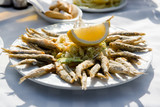 Plate of deep fried anchovies with lemon and salad