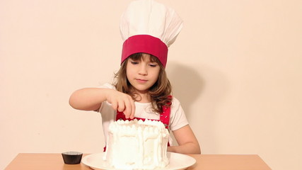 little girl cook decorates a cake