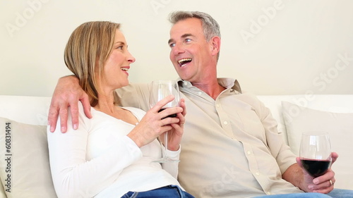 Mature couple drinking red wine together on the couch